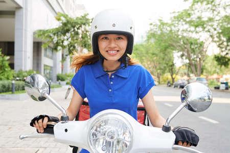 Porträt eines weiblichen glücklichen Essenskuriers auf dem Roller, der es eilig hat, das Mittagessen zu liefern?