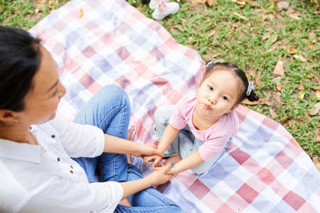 Mother sitting in park with daughter on laps and playing games on digital tablet