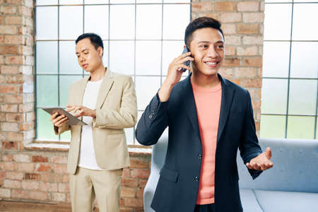 Portrait of young cheerful Vietnaemese businessman talkig on phone, his colleague working on tablet computer in background