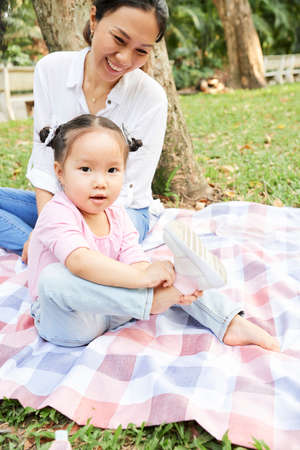 Happy mother looking at little daughter taking off sneakers as she is sitting on blanket in city park
