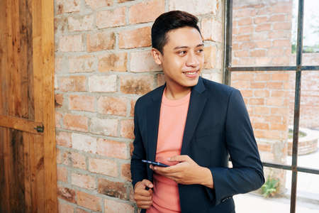 Portrait of handsome smiling business executive with smartphone standing at office window