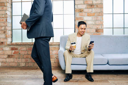 Handsome young business executive sitting on sofa with cup of coffee and reading text message
