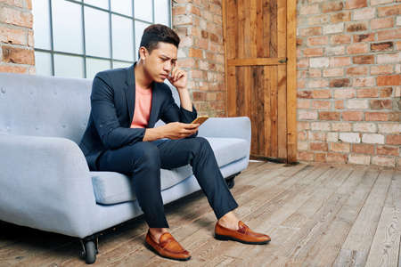 Frowning young Asian businessman reading message with bad news on his smartphone