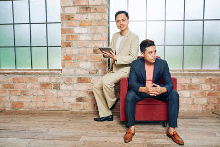 Young confident Asian business people starting new project in almost empty loft office 版權商用圖片