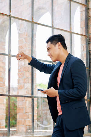 Happy young Asian entrepreneur with smartphone leaning on office window and looking outside