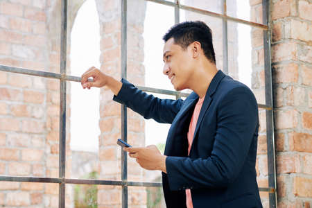 Positive young Vietnamese business executive with smartphone in hand looking through big window in loft office Imagens