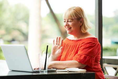 Cheerful mature woman waving with her hand when making videocall Reklamní fotografie