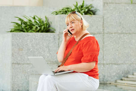 Nervous mature woman sitting on steps with laptop and talking on phone