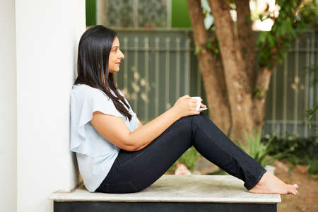 Pensive young Asian woman sitting on porch and enjoying calm morning with cup of coffee 版權商用圖片
