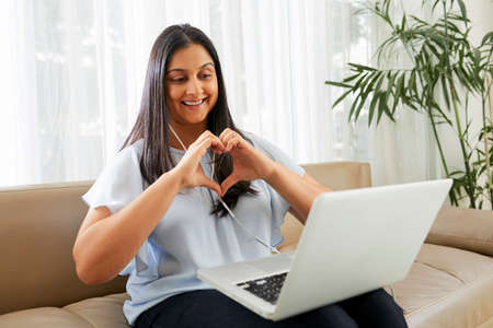 Happy woman making heart shape with her hands when video calling boyfriend