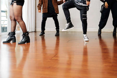 Legs of professional dancers training together on wooden parquet floor