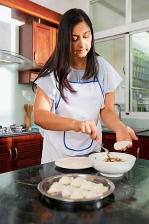 Housewife in apron putting delicious filling in ravioli dough