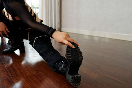 Professional female dancer in leather boots stretching feet and legs before training in class