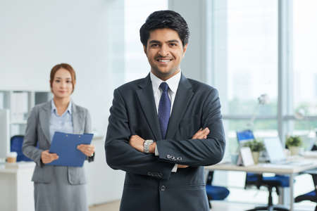 Portrait of Indian successful leader standing in suit with his arms crossed and smiling at camera with young businesswoman in the background Imagens