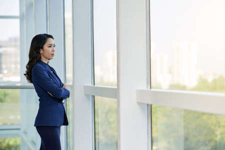 Young Asian businesswoman standing with arms crossed near the big window at office looking at view of the city and thinking about something 写真素材