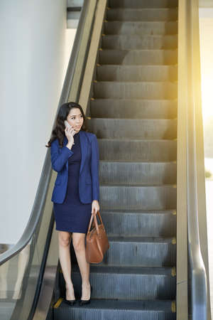 Asian beautiful businesswoman has a conversation on mobile phone while standing on escalator at office building