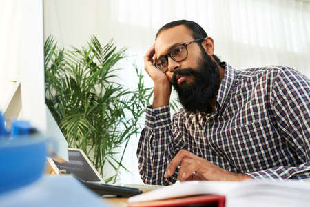 Bearded young office worker in eyeglasses sitting at office desk looking at computer monitor and tired of his work