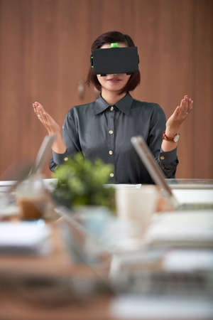Young confident businesswoman sitting at the table in VR goggles and gesturing during virtual meeting in board room