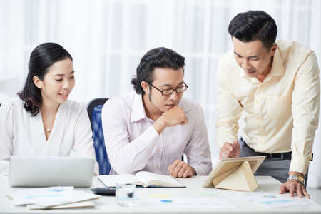 Asian young male leader showing online presentation on digital tablet to his business partners while they sitting at the table at business meeting