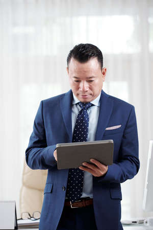 Asian mature businessman wearing suit standing and concentrating on his work on digital tablet at his office 免版税图像