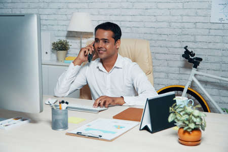 Indian manager sitting at his workplace typing on computer keyboard while talking on mobile phone and smiling at office
