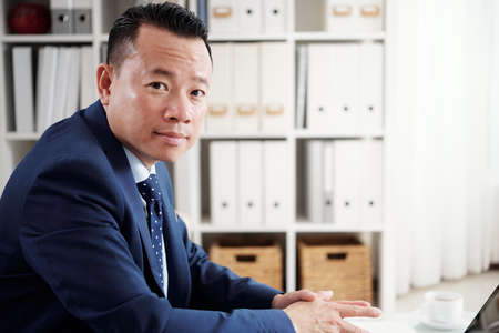 Portrait of Asian mature businessman in suit looking at camera while working on laptop at office Stock Photo