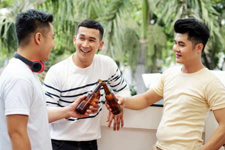 Happy positive Vietnamese young men talking bottle beer and discussing news outdoors 版權商用圖片