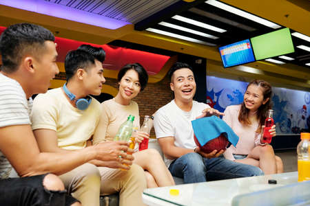 Happy young Asian man wiping bowling ball and taking with friends