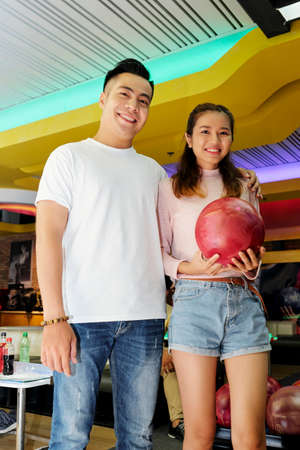 Portrait of happy young Asian boyfriend and girlfriend with bowling ball
