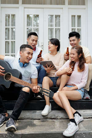 Cheerful young Asian people sitting on house porch, drinking beer and singing song