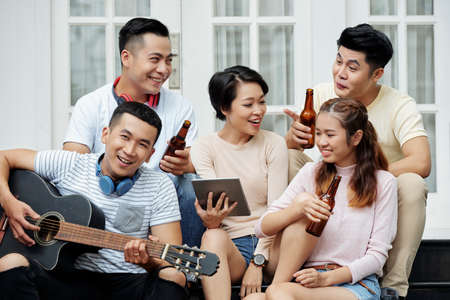 Group of young Vietnamese people drinking beer, talking and singing together