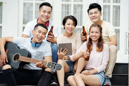 Cheerful Asian men and women sitting on house porch with guitar and beer bottles 版權商用圖片