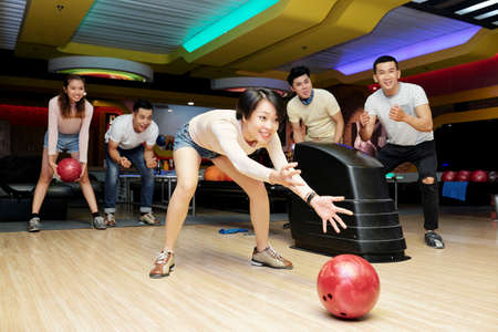 Clumsy pretty young Asian woman throwing heavy ball on bowling alley 版權商用圖片