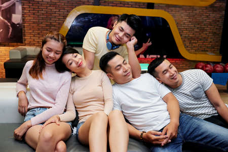 Smiling young Asian people leaning on each other and sleeping after playing bowling Standard-Bild