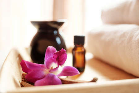 Essential oil and orchid flower on tray in massage spa salon