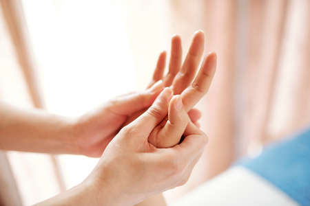 Close-up image of young woman enjoying hand massage with oils