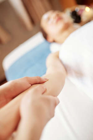 Specialist doing relaxing arms massage to young female client, selective focus