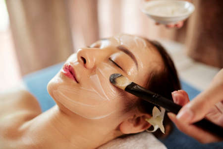 Face of young Asian woman getting moisturizing face treatment in beauty salon