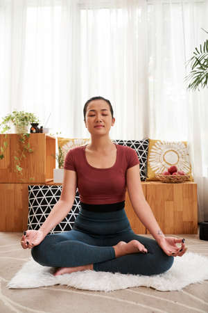 Young Asian woman sitting in lotus on yoga mat in living room