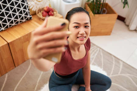 Young Asian woman clogging or photographing herself after exercising at home