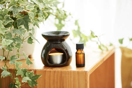 Aromalampe mit brennender Kerze und ätherischem Öl auf Holztisch