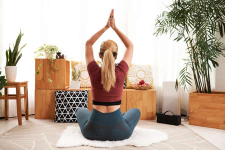 Young woman raising hand in namaste gesture when sitting in lotus posing on rag in living room, view from the back