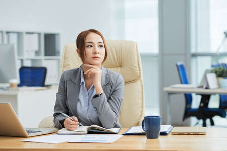 Serious Asian businesswoman sitting at her workplace with notepad and thinking over new business ideas at office