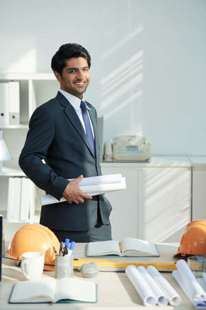 Portrait of Indian architect in suit holding blueprints standing near his workplace and smiling at camera at office