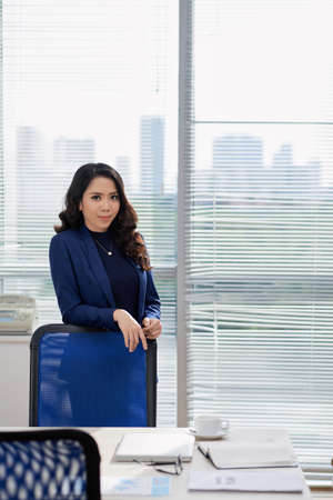 Portrait of Asian young businesswoman standing near the table and looking at camera during business meeting at office