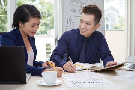 Smiling Asian businessman using tablet pc and talking to businesswoman who pointing at business plan while they working at office together