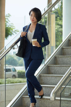 Young Asian businesswoman holding disposable cup of coffee and walking down the stairs of modern office after her work day