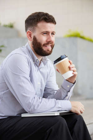 Smiling bearded businessman sitting on stairs outdoors with tablet pc on his knees and enjoying coffee from disposable cup