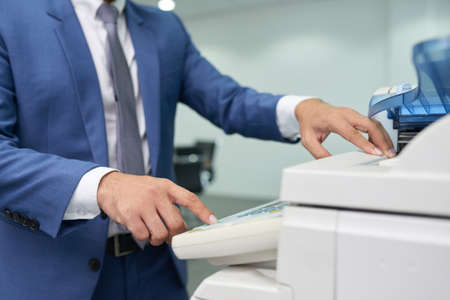 Close-up of businessman in suit standing near the copy machine and making a copy of document at office