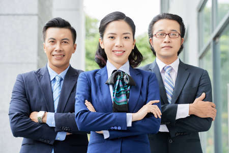 Portrait of Asian successful business people with businesswoman in head standing with arms crossed and smiling outdoors Stock Photo